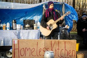 "Coffee and a song for the homeless on Trafalgar Square. Photo: Homeless Kitchen by <a href=""https://www.flickr.com/photos/garryknight/"">Garry Knight</a>  Creative Commons <a href=""https://creativecommons.org/licenses/by/2.0/"">Attribution 2.0 Generic</a>  Photo <a href=""https://www.flickr.com/photos/garryknight/15779823714/in/photolist-yo5YZa-D6QjNL-8WmzKu-q3pHQ7-dB1vYu-7Y267Y-FwCkk5"">Link"